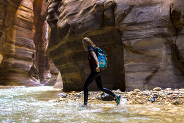 Portrait of female backpacker walking in river by mountains - CAVF28386