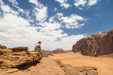 Woman sitting on rock against sky on sunny day - CAVF28392
