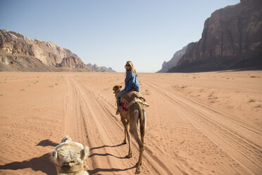 Female tourist looking over shoulder while riding on camel in desert - CAVF28395
