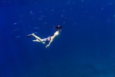 Man swimming underwater in sea - CAVF28413