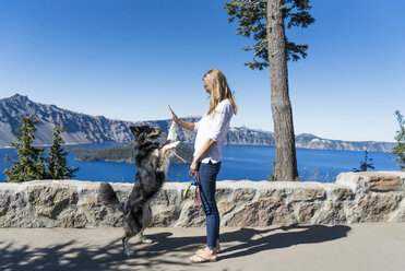Woman giving high-five to playful dog while standing against lake - CAVF28419