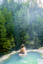High angle view of woman swimming in hot spring at forest - CAVF28425