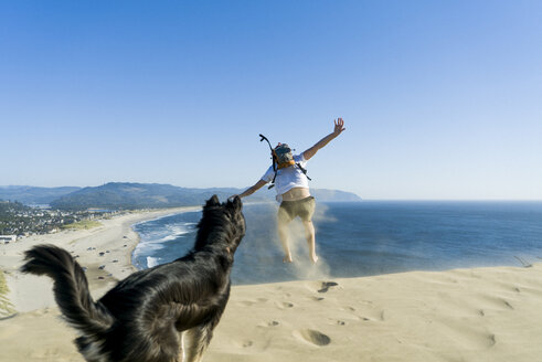 Playful man jumping while dog standing at beach against clear blue sky - CAVF28434