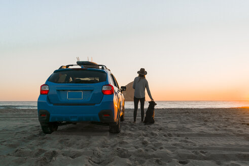 Rear view of woman with dog standing by car at beach - CAVF28437