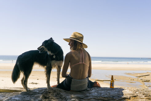Rear view of happy woman with dog enjoying at beach - CAVF28446