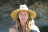 Close-up portrait of woman in sun hat at beach - CAVF28449