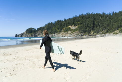 Man holding surfboard with dog walking at beach - CAVF28452