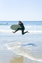 Man with surfboard jumping in sea against clear sky - CAVF28455