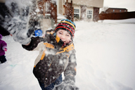 Portrait of happy boy playing with snow in yard - CAVF28524