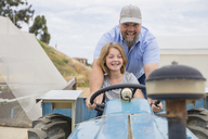 Farmer showing his daughter, how to drive a tractor - ZEF15228