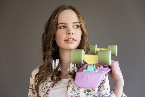 Portrait of teenage girl with pink skateboard - FMKF04990
