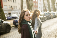 Portrait of teenage girl walking hand in hand with her best friend on the street - FMKF04999