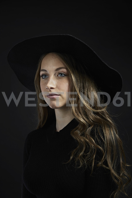 Portrait of young woman wearing black hat and clothes against black background - PDF01556
