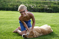 Happy teenage boy playing with dog in grass - LBF01867