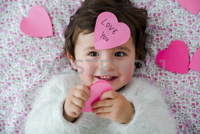 Portrait of baby girl with pink heart-shaped post it stickers - GEMF01904