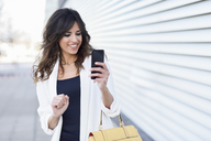 Portrait of smiling businesswoman using cell phone - JSMF00134