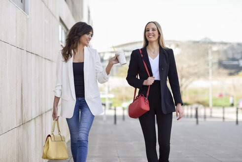 Two smiling businesswomen with handbags and coffee to go walking on pavement - JSMF00140