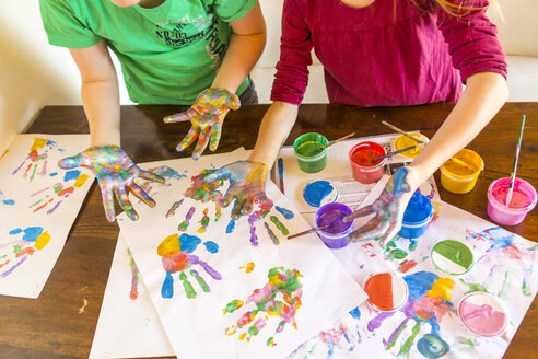 Girl and boy playing with finger paint, hand prints - SARF03624
