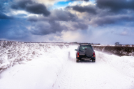 United Kingdom, Scotland, East Lothian, North Berwick, snowdrifts, off road vehicle during winter storm - SMAF00993