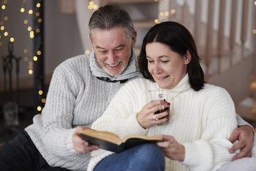 Happy mature couple reading a book in living room - ABIF00190
