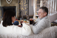 Happy mature couple with hot drinks in living room - ABIF00193
