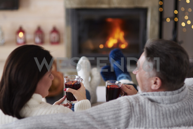 Mature couple with hot drinks in living room at the fireplace - ABIF00196