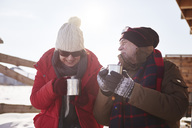 Happy mature couple with hot drinks outdoors at mountain hut  in winter - ABIF00202