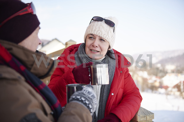 Mature couple with hot drinks talking outdoors in winter - ABIF00205