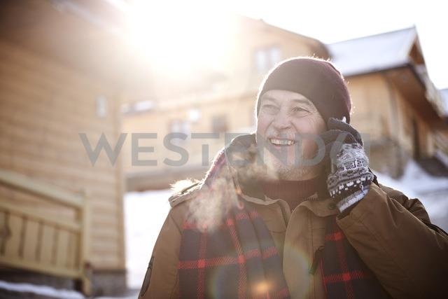 Smiling senior man talking on cell phone in mountain village in winter - ABIF00211