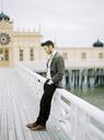 Groom wearing tuxedo leaning against railing on pier - FOLF00575