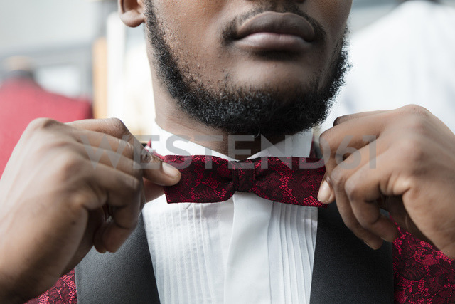 Close-up of a man wearing tuxedo in tailor shop adjusting the bow tie - LFEF00105