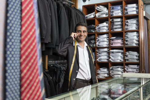 Smiling elegant tailor talking on phone in tailor shop - LFEF00111