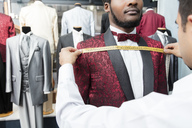 Tailor measuring up client wearing tuxedo in tailor shop - LFEF00114