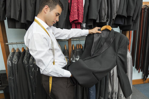 Tailor examining suit jacket in tailor shop - LFEF00117