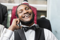 Elegant man talking on phone and laughing in tailor shop - LFEF00123