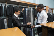 Tailor showing ties to client in tailor shop - LFEF00132