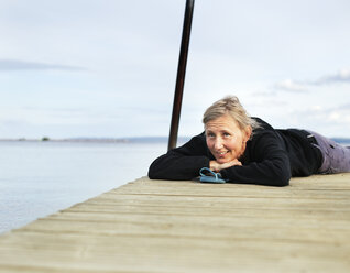 Mature woman lying down on wooden jetty - FOLF00775
