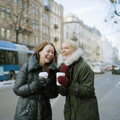 Two women holding disposable coffee cups laughing - FOLF00802
