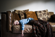 Boy sleeping on couch at home against wall - CAVF28534