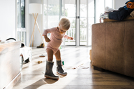 Toddler wearing rubber boots while sucking pacifier at home - CAVF28537