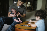 Baby boy playing guitar while sitting by father and newborn brother at home - CAVF28564