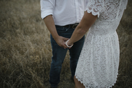 Midsection of couple holding hands while standing on field - CAVF28573