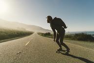 Full length of man skateboarding on country road - CAVF28627