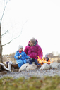 Mother with son sitting on log by campfire - FOLF01085
