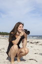 Teenage girl taking pictures on beach - FOLF01217