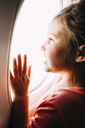 Curious girl looking through airplane window - CAVF28695
