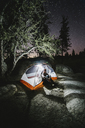 Hiker sitting in illuminated tent on rock by trees at night - CAVF28743