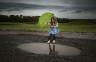 Girl holding umbrella while walking into puddle on road against stormy clouds - CAVF28746
