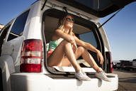 Thoughtful woman sitting in car trunk during vacation - CAVF28752