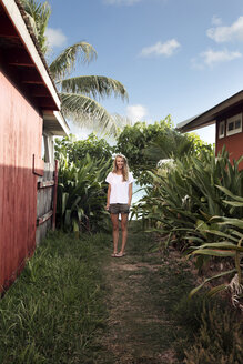 Portrait of happy woman standing amidst beach cabins - CAVF28773